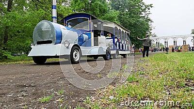 NIKOPOL, UKRAINE - MAI 2019 : Le train des enfants roule les enfants en parc les prochains parents prennent des photos de leurs e clips vidéos