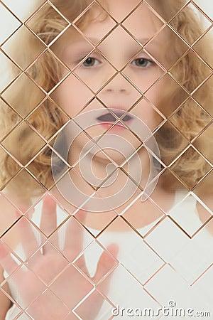 Niño autístico enmascarado detrás del cristal del vidrio