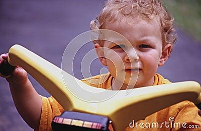 Niño pequeño en el juguete del montar a caballo