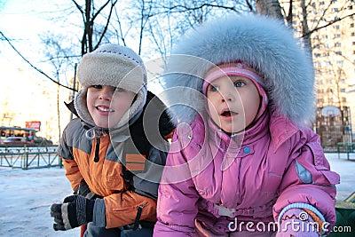 Niño pequeño y muchacha en la calle en el invierno 2