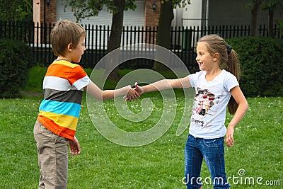 Niño pequeño y muchacha que sacuden las manos en el parque, al aire libre