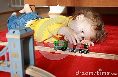 Niño que juega con los trenes en casa