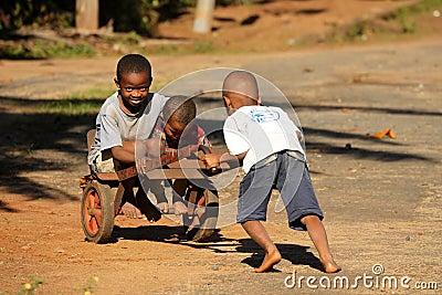Niños con una carretilla Imagen editorial