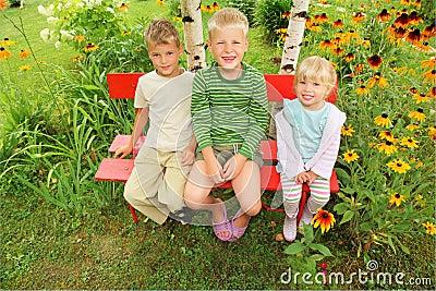 Niños que se sientan en banco en jardín