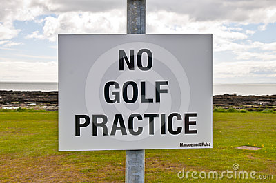 No golf practice sign with clouds, grass and sky