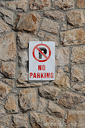 No Parking Sign on Stone Wall