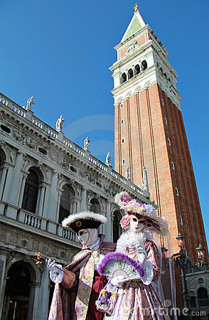 Noble masked couple under Bell tower of San Marco Editorial Image