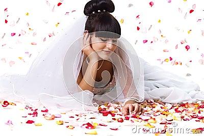Noiva bonita e pétalas cor-de-rosa