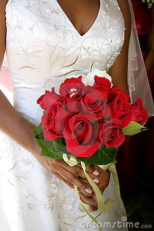 Noiva com anéis de casamento no ramalhete vermelho