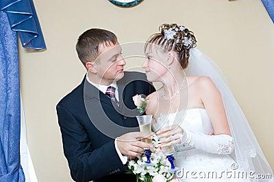 Noiva e noivo com vidros do champanhe