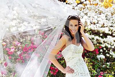 Noiva na frente das flores com véu