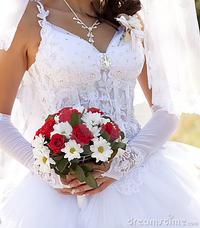 Noiva que prende as rosas vermelhas bonitas que wedding o ramalhete