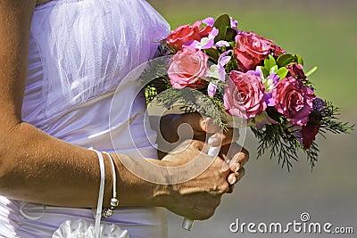 Noiva que prende o ramalhete bonito das flores
