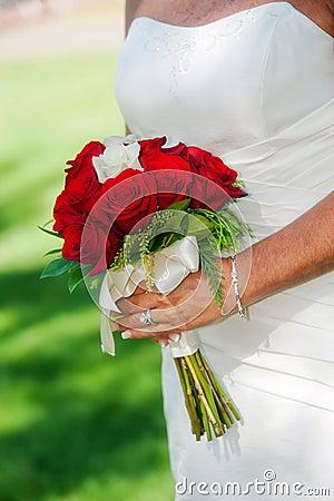 Noiva que prende o ramalhete cor-de-rosa do vermelho