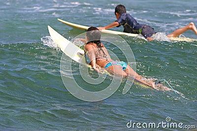 девушка мальчика идет детеныши Гавайских островов занимаясь серфингом