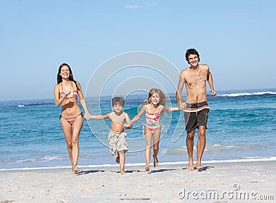 Νέα οικογένεια που τρέχει κατά μήκος της παραλίας στις διακοπές
