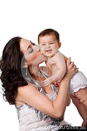 婴孩面颊愉快的亲吻的母亲
