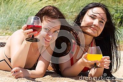 Δύο νέα κορίτσια πίνουν τα κοκτέιλ στην παραλία