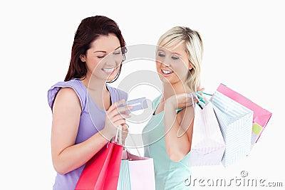 Εύθυμες γυναίκες με τις τσάντες αγορών και μια κάρτα