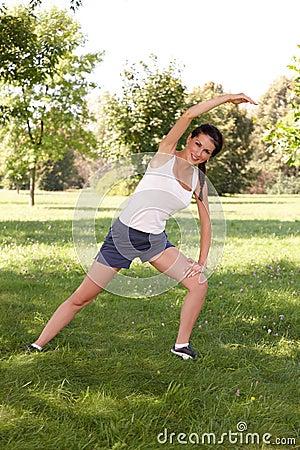 Молодая женщина делая протягивающ тренировку на траве