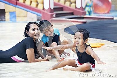 ασιατική οικογενειακή ευτυχής λίμνη που θέτει την κολύμβηση