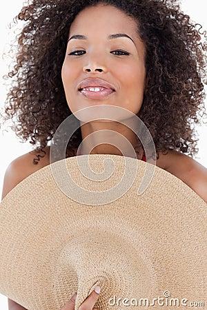 隐藏她的在帽子之后的可爱的妇女身体