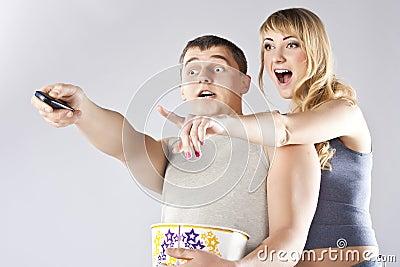 吃玉米花电视注意的年轻人的夫妇