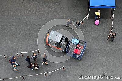 Οι άνδρες και οι γυναίκες περνούν το αυτοκίνητο πρίν προσγειώνονται στο σκάφος της γραμμής Εκδοτική εικόνα