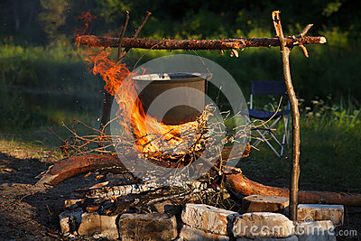 Προετοιμασία των τροφίμων στο μεγάλο δοχείο στην πυρά προσκόπων