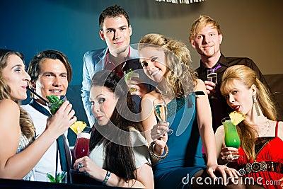 Люди в коктеилах клуба или штанги выпивая
