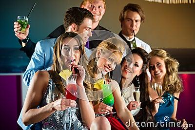 俱乐部或棒饮用的鸡尾酒的人们