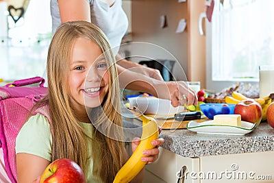 Οικογένεια - μητέρα που κάνει το πρόγευμα για το σχολείο