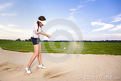 女孩切削在地堡的高尔夫球运动员球。