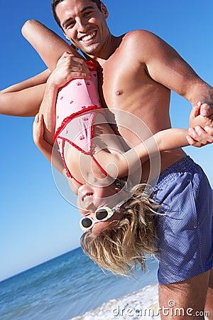 获得的父亲和的女儿在海滩的乐趣