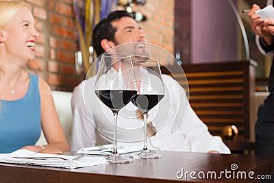 耦合在餐馆或棒的饮用的红葡萄酒