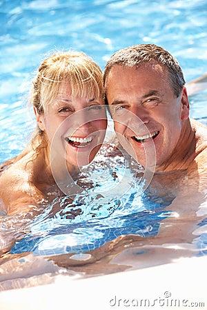 高级夫妇获得乐趣在游泳池