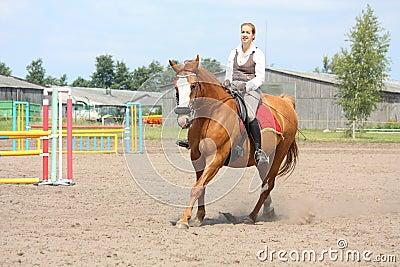 美丽的幼小白肤金发的妇女骑马栗子马