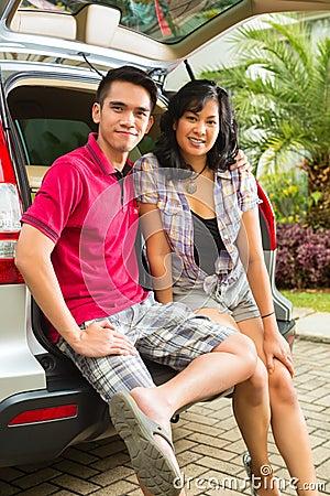 亚洲夫妇是愉快的在前面汽车