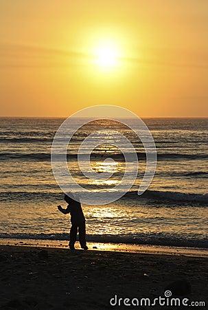 儿童投掷的石头到海洋里