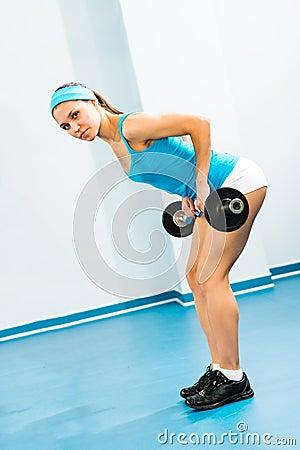 Молодая женщина делая культуризм в спортзале