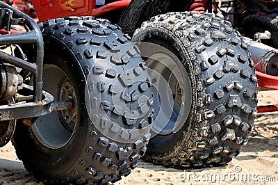在海滩沙子的摩托车轮胎
