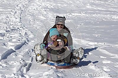母亲和子项获得乐趣下滑在雪撬小山下