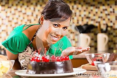 亚洲妇女可可浆蛋糕在厨房里
