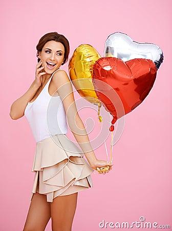 有心形的气球的活泼的妇女
