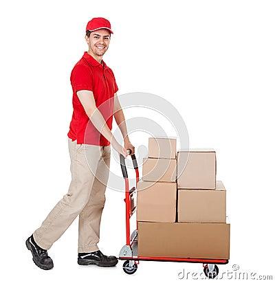 Работник доставляющее покупки на дом с вагонеткой коробок