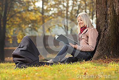 坐在公园和读故事的新母亲对她的婴孩