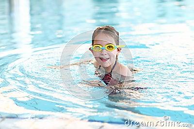 有风镜的女小学生在游泳池