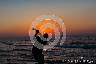 高尔夫球运动员摇摆的日出海洋