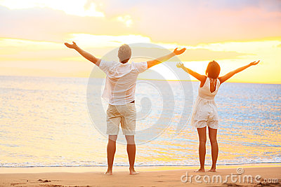 享受日落的愉快的欢呼的夫妇在海滩