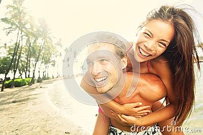 愉快年轻快乐夫妇海滩乐趣笑